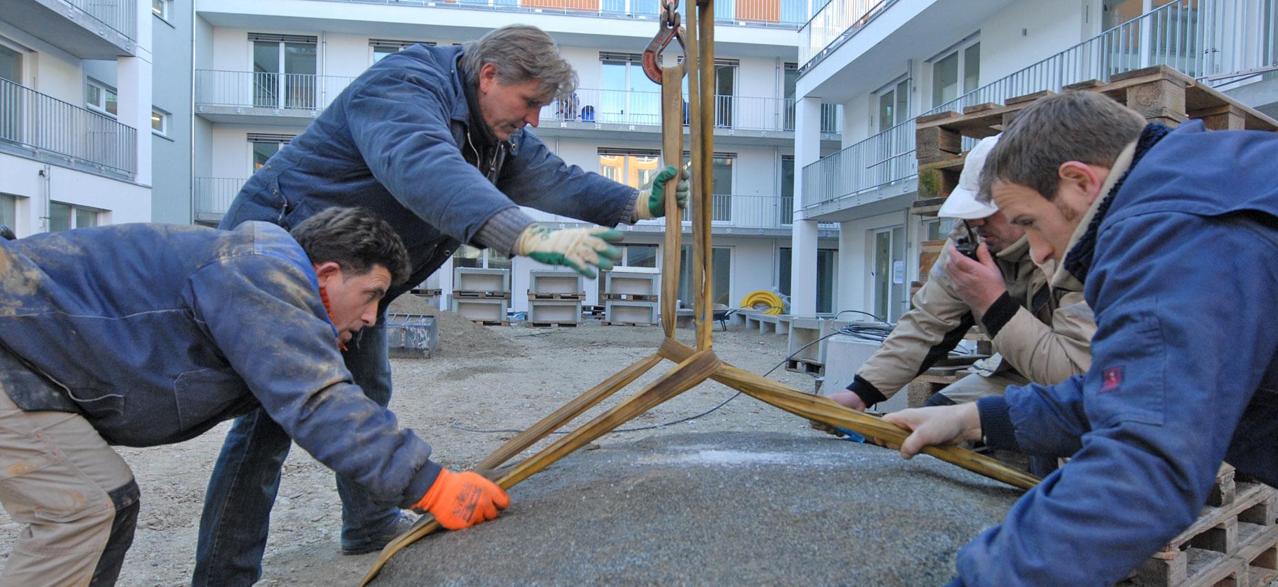 Bauarbeiter beim Anheben und Versetzen eines Steins für die Gestaltung der Außenanlagen der studiosus Studentenapartments in München
