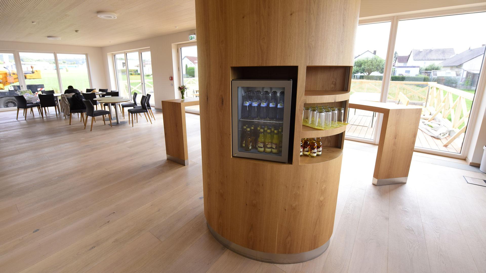 Ruhe- und Essbereich mit Holzsäule mit integriertem Kühlschrank und Regalfächern sowie Sitzgruppen im Hintergrund – harmonische Raumgestaltung durch Innenarchitektin Barbara Jurk von atelier8 in Frankfurt
