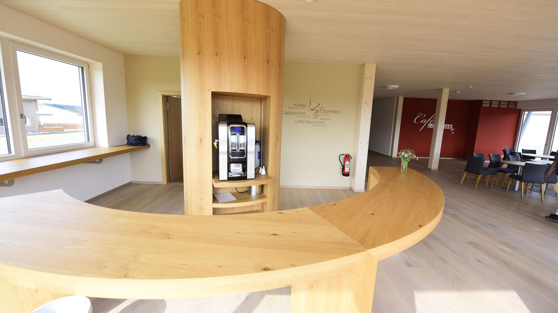 Café-Lounge mit Holztresen sowie Sitzgruppen im Hintergrund – harmonische Raumgestaltung durch Innenarchitektin Barbara Jurk von atelier8 in Frankfurt