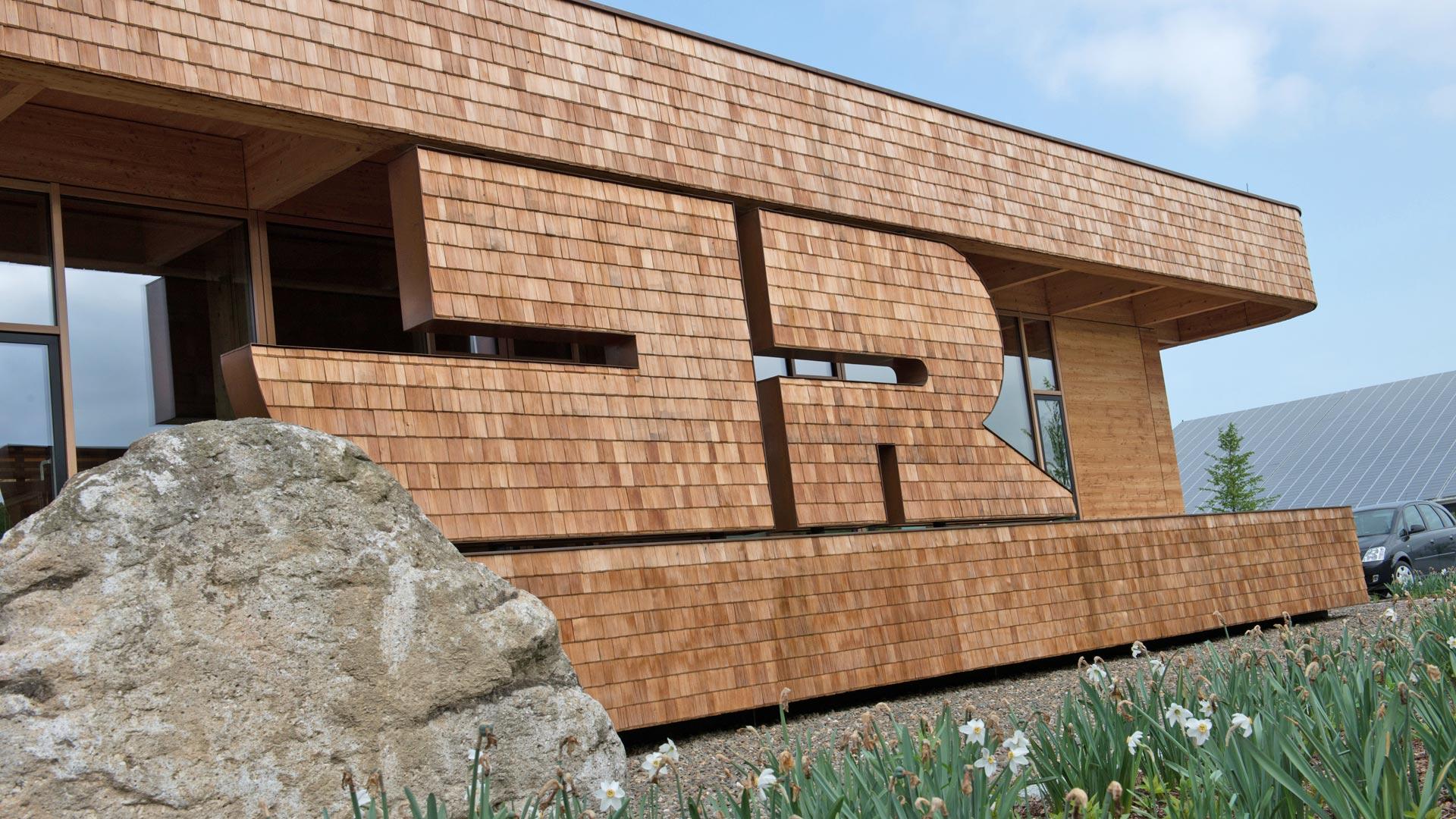 aus Holz gefertigtes Firmenlogo integriert in der Fassade des Firmengebäudes der Josef Rädlinger GmbH