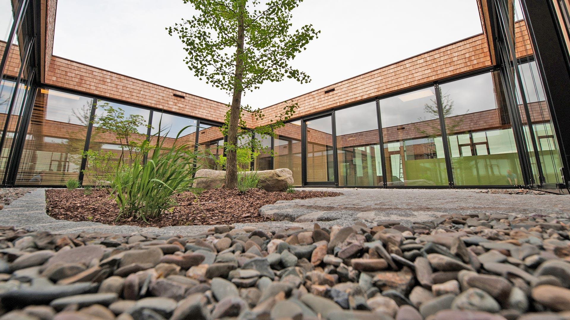 Gestaltung des Innenhofs eines Firmengebäudes nach Feng Shui und Geomantie mit Naturstein und Bepflanzung durch das Architekturbüro atelier8 in Frankfurt