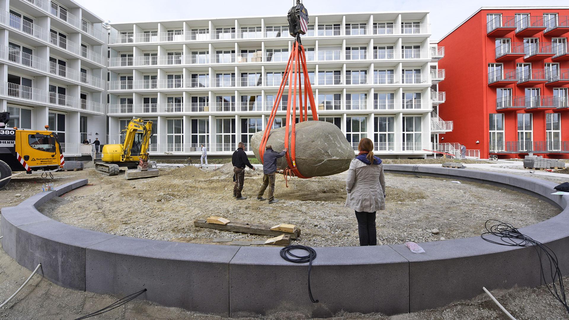 Kran und Bauarbeiter bei der Herzsteinsetzung im Gartenbereich der studiomuc Apartmenthäuser überwacht durch Barbara Jurk vom Architekturbüro atelier8
