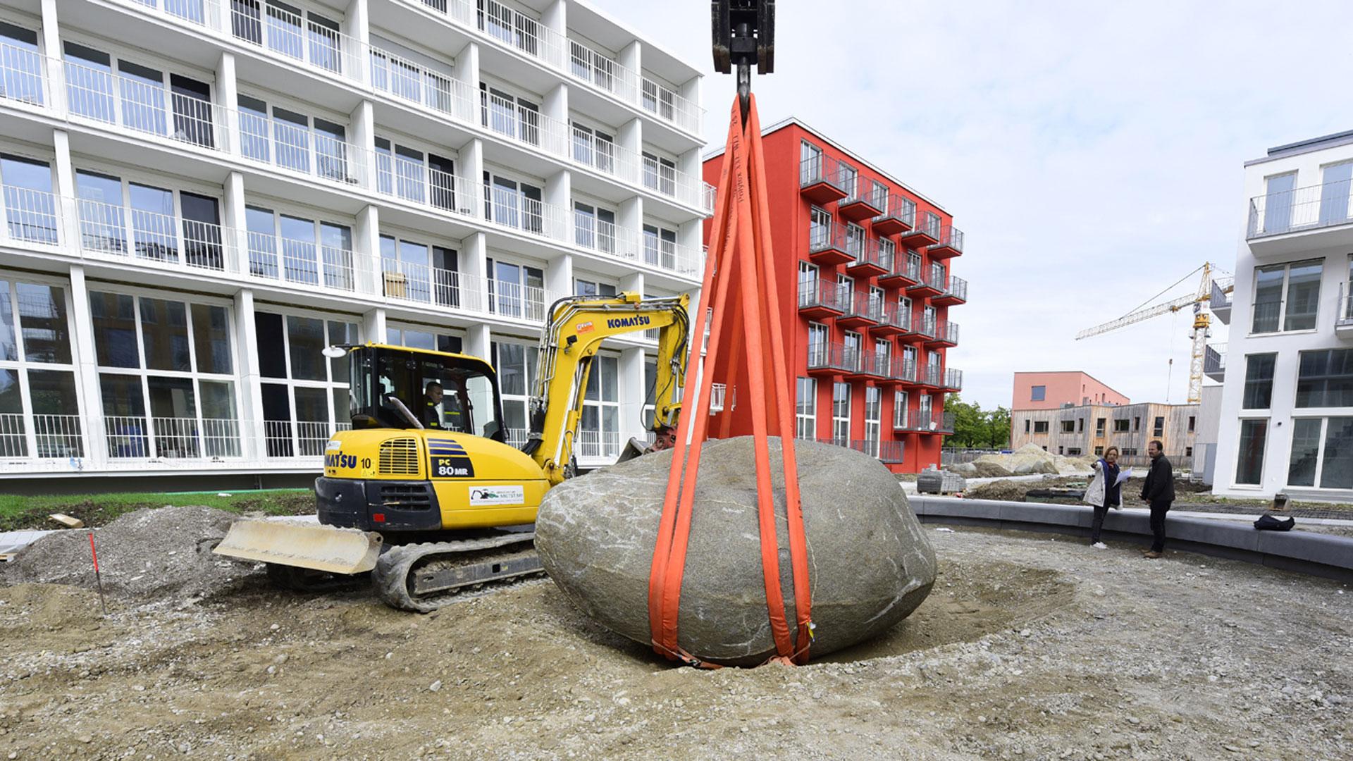 Kran und Bauarbeiter bei der Herzsteinsetzung im Gartenbereich der studiomuc Apartmenthäuser unter Anweisung von Barbara Jurk vom Architekturbüro atelier8