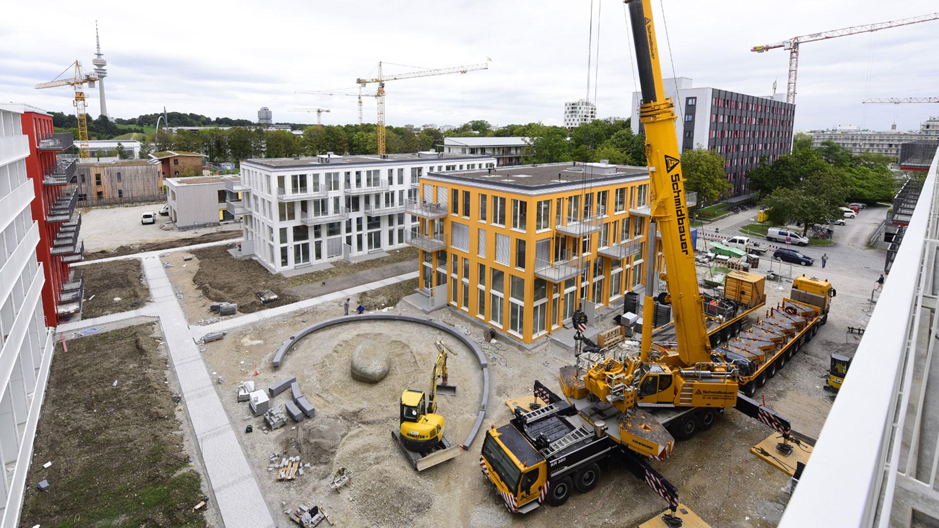 Ansicht der Baustelle der studiomuc Apartmenthäuser während der Bauarbeiten an den Außenanlagen zur Herzsteinsetzung durch das Architekturbüro atelier8 Barbara Jurk